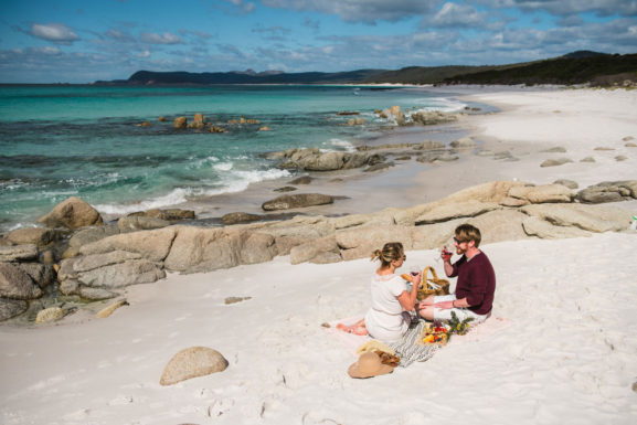 A man and a woman having a picnic and wine on a secluded beach with a beautiful backdrop of mountains